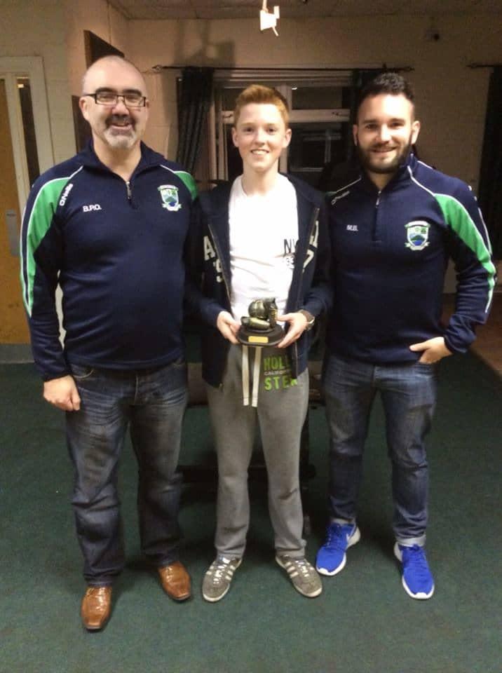 Ciarán Mackin receives his U14 Player of the Year award from Brendy Osborne and Micheál Brady.