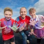 Calum and Alex McShane shower Lord Mayor of Armagh, Banbridge and Craigavon, Councillor Darryn Causby with colour in a sunny Lurgan Park
