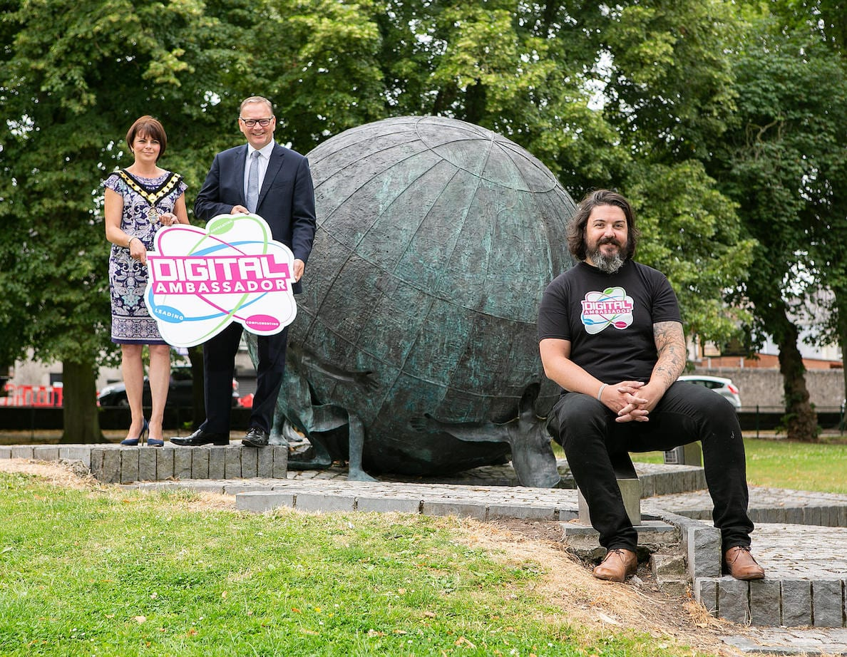 Armagh City, Banbridge and Craigavon Borough Council has appointed Aaron Taylor, a founding member of Belfast's Ormeau Baths start-up hub and currently managing partner at Frankly, to the new role of Digital Ambassador. With a wealth of experience in the sector as an advisor to several digital and tech companies in London and Belfast, Aaron, also a co-founder of the highly-successful ICONS Festival, will now spearhead a new era of digital innovation and collaboration across the borough. The Council, which earlier this year pitched for and secured £2.4 million of UK government funding to help increase broadband speeds and boost borough-wide connectivity, has a clear digital strategy and a commitment to deliver it. Informed through extensive engagement with organisations at the heart of Northern Ireland's most innovative sectors and businesses, including Catalyst Inc., Matrix and Digital Catapult, in addition to universities, higher and further education colleges, local enterprise agencies and Invest NI, the Council's strategy is focused on building digital skills, capability and supporting this key growth sector and will be championed by Aaron over the course of a three-year delivery period. Pictured announcing his appointment are Councillor Julie Flaherty, Lord Mayor and Roger Wilson, Chief Executive of Armagh City, Banbridge and Craigavon Borough Council with new Digital Ambassador Aaron Taylor.